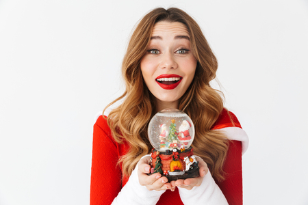 Portrait of joyful woman 20s wearing Santa Claus red costume smiling and holding Christmas snow ball isolated over white background