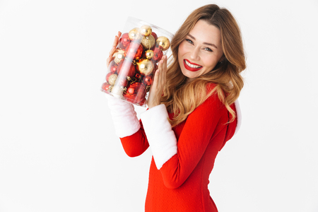 Portrait of optimistic woman 20s wearing Santa Claus red costume smiling and holding Christmas tree decorations isolated over white background Stock Photo