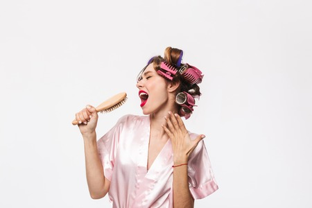 Cheerful housewife with curlers in hair wearing robe standing isolated over white background, holding hairbrush, singing