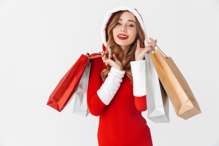 Portrait of cheerful woman 20s wearing Santa Claus red costume smiling and holding colorful paper shopping bags with purchases isolated over white background Stock Photo