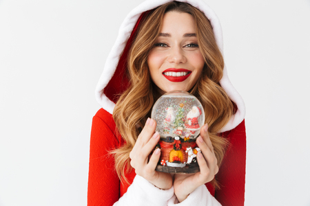 Portrait of young woman 20s wearing Santa Claus red costume smiling and holding Christmas snow ball isolated over white background