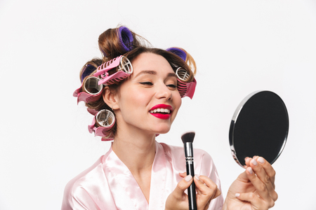Beautiful housewife with curlers in hair wearing robe standing isolated over white background, applying makeup with a brush Stock Photo
