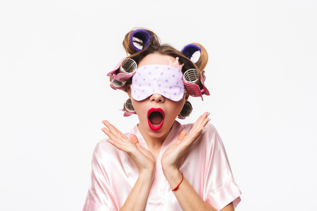 Tired housewife with curlers in hair wearing robe yawning isolated over white background, wearing sleep mask