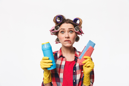 Upset housewife with curlers in hair standing isolated over white background, holding detergents Фото со стока - 116700275