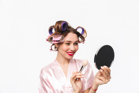 Beautiful housewife with curlers in hair wearing robe standing isolated over white background, applying makeup with a brush 스톡 콘텐츠