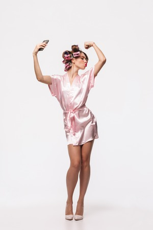 Full length portrait of a pretty housewife with curlers in her hair wearing robe standing isolated over white background, taking a selfie with mobile phone
