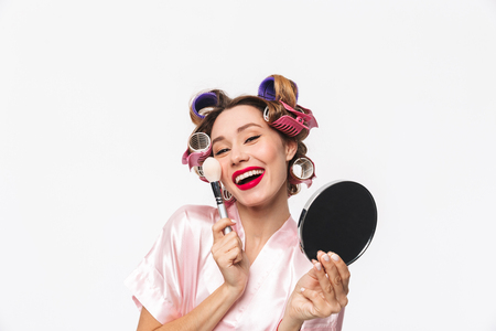 Beautiful housewife with curlers in hair wearing robe standing isolated over white background, applying makeup with a brush 版權商用圖片