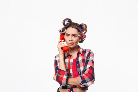 Disappointed housewife with curlers in hair standing isolated over white background, talking on a landline phone