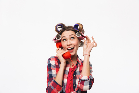 Cheerful housewife with curlers in hair standing isolated over white background, talking on a landline phone