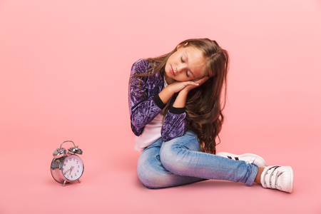 Pretty little girl sitting isolated over pink background, sleeping while sitting with an alarm clock