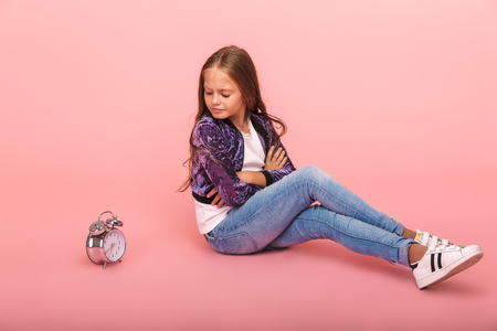 Pretty upset little girl sitting isolated over pink background, s sitting with an alarm clock
