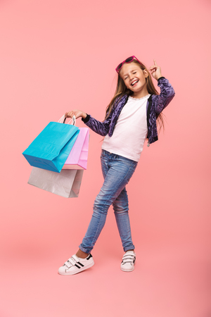 Cheerful little girl isolated over pink background, carrying shopping bags Reklamní fotografie