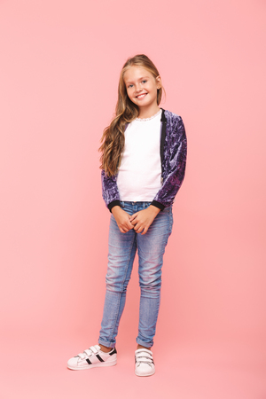 Full length of a smiling little girl standing isolated over pink background