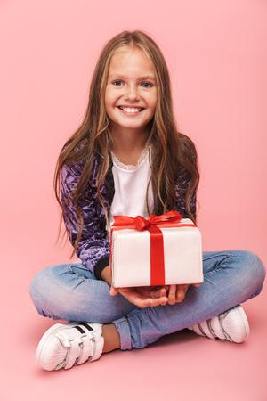 Hübsches kleines Mädchen, das isoliert über rosafarbenem Hintergrund sitzt und Geschenkbox hält Standard-Bild