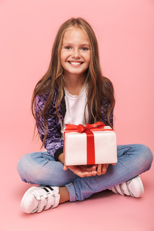 Pretty little girl sitting isolated over pink background, holding gift box
