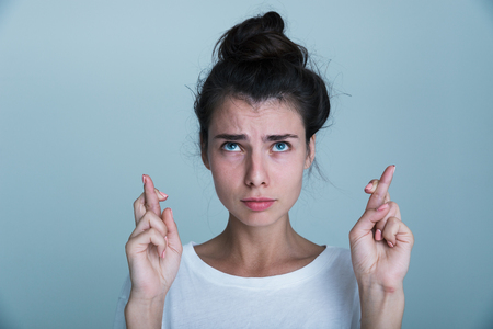 Portrait of a casual beautiful young girl isolated over blue background, holding fingers crossed for good luck