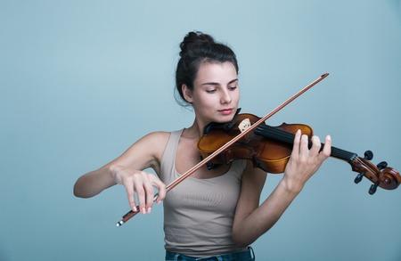Close Up retrato de una joven y bella mujer posando con un violín aislado sobre fondo azul.