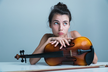 Portrait of a tired beautiful young woman sitting at the table with a violin isolated over blue background Banque d'images
