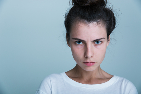 Close up of an upset young casual girl isolated over blue background