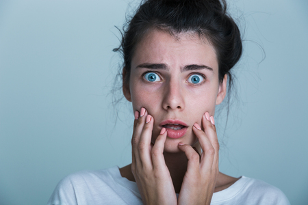 Close up of a shocked young woman wearing t-shirt isolated over blue background