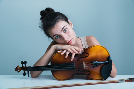 Portrait of a beautiful young woman sitting at the table with a violin isolated over blue background Reklamní fotografie