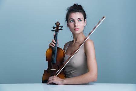 Porträt einer schönen jungen Frau, die mit einer Geige am Tisch sitzt, isoliert auf blauem Hintergrund