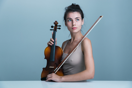 Portrait of a beautiful young woman sitting at the table with a violin isolated over blue background Reklamní fotografie - 116701721