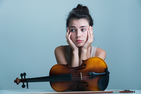 Portrait of a beautiful young woman sitting at the table with a violin isolated over blue background Stok Fotoğraf