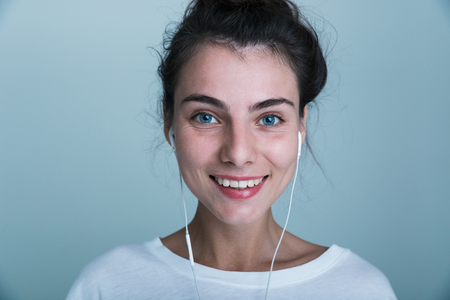 Close up of a beautiful young casual girl standing isolated over blue background, listening to music with earphones