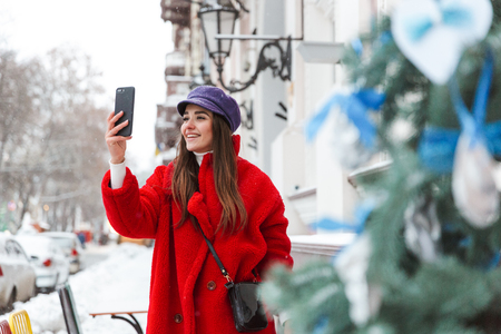 Image of a pretty young woman outdoors walking at snow winter street take selfie by mobile phone.