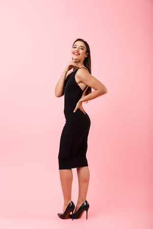 Full length portrait of a beautiful young woman wearing black dress standing isolated over pink background, posing 免版税图像