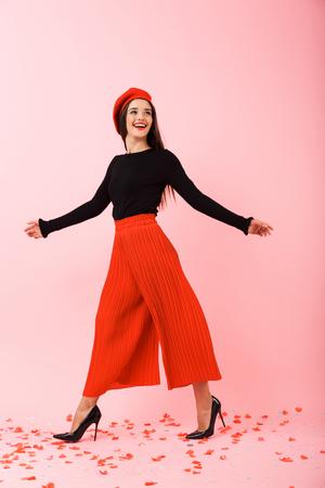 Volledig lengteportret van een mooie jonge vrouw die rode baret en zonnebril draagt die geïsoleerd over roze achtergrond lopen