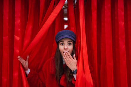 Image of a pretty young woman looks out between red curtain. Stok Fotoğraf