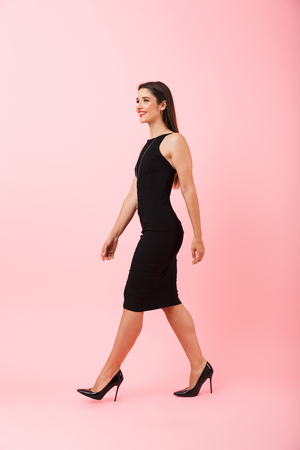 Portrait de pleine longueur d'une belle jeune femme vêtue d'une robe noire marchant isolée sur fond rose, célébrant le succès