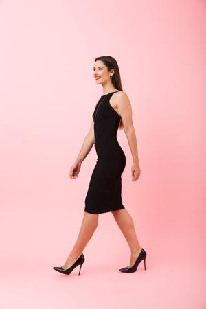 Volle Längsansicht Porträt einer schönen jungen Frau in schwarzem Kleid, die einzeln über rosafarbenem Hintergrund geht und den Erfolg feiert
