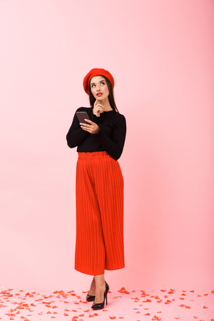 Full length portrait of a pensive beautiful young woman wearing red beret standing isolated over pink background Stock Photo