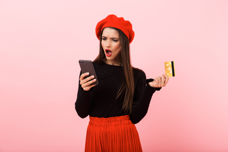 Portrait of an angry beautiful young woman wearing red beret standing isolated over pink background, looking at mobile phone, holding plastic credit card Banque d'images