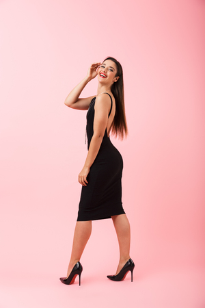Full length portrait of a beautiful young woman wearing black dress standing isolated over pink background, posing Foto de archivo