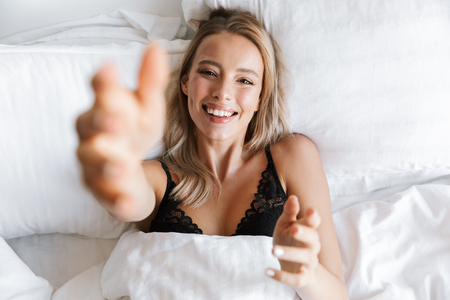 Photo of an amazing beautiful young woman in lingerie underwear lies in bed at home raises hands to camera.