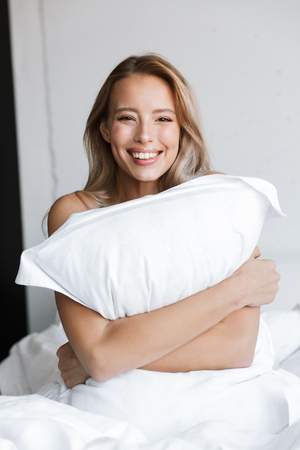 Photo of an amazing beautiful young woman in lingerie underwear at morning in bed at home holding pillow.