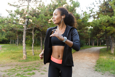 Image of american sportswoman 20s wearing black tracksuit and headphones working out while running through green park Reklamní fotografie