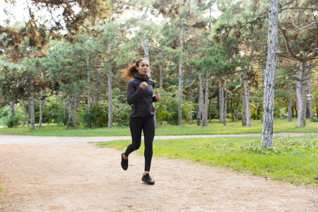 Image of sportswoman 20s wearing black tracksuit working out while running through green park Reklamní fotografie