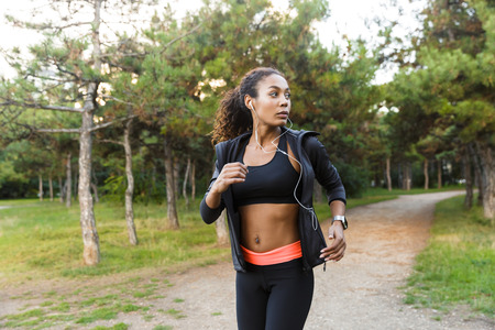 Image of american girl 20s wearing black tracksuit and earphones working out while running through green park