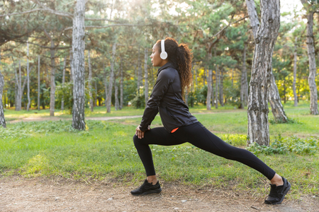 Image of sportswoman 20s wearing black tracksuit working out and stretching body in green park