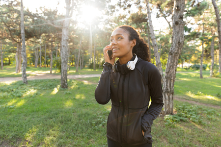 Image of joyful woman 20s wearing black tracksuit and headphones using cell phone while walking through green park