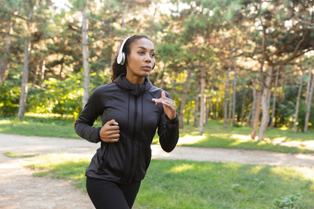 Image of energetic woman 20s wearing black tracksuit and headphones working out while running through green park Stock fotó