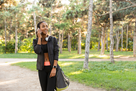 Image of sporty woman 20s wearing black tracksuit and headphones speaking on mobile phone while walking through green park Stockfoto