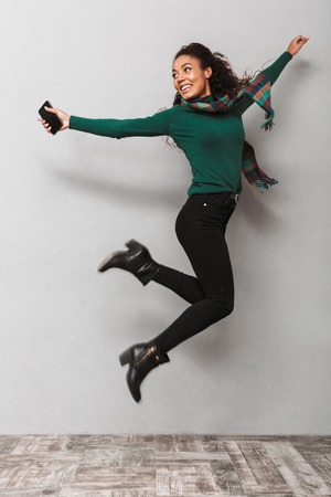 Full length portarit of a pretty african woman wearing scarf jumping over gray background, holding mobile phone