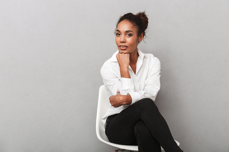 Attractive young african business woman wearing shirt sitting in a chair isolated over gray background