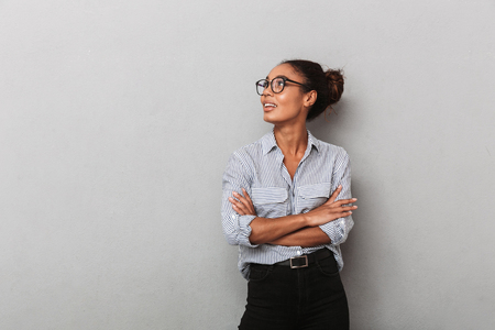 Confident african business woman wearing eyeglasses and shirt standing isolated over gray